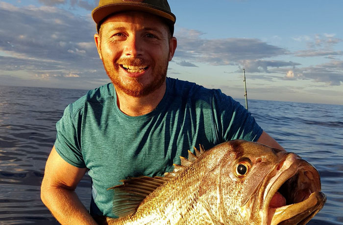 Smiling with the catch on a fishing charter