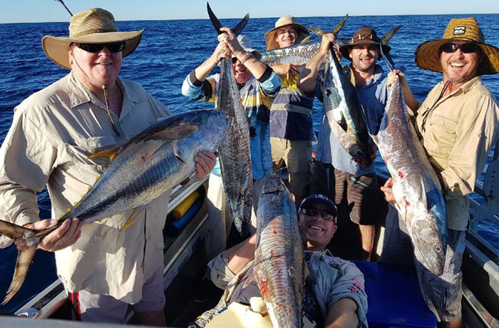 6 people posing with their catch on the boat